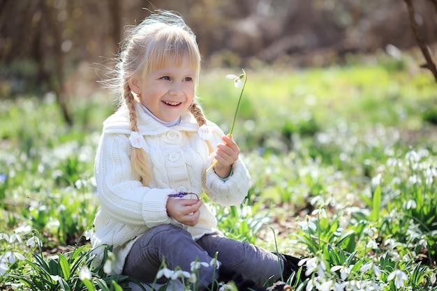 Piękna dziewczyna siedzi na przebiśniegi łąki kwiat. piękna mała dziewczynka w białym swetrze z dzianiny spaceruje wiosną po lesie. czas wielkanocy
