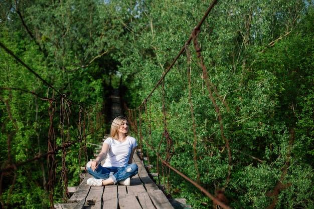 Piękna dziewczyna siedzi na starym drewnianym moście. weekend i wakacje w parku lato.