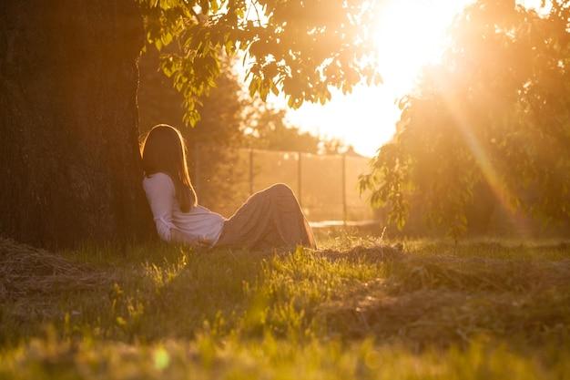 Piękna dziewczyna siedzi pod drzewem i ogląda zachód słońca