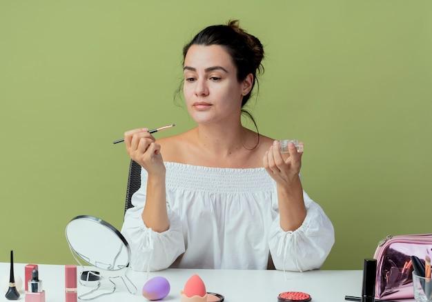 Piękna dziewczyna siedzi przy stole z narzędziami do makijażu gotowymi do nałożenia cienia do powiek pędzlem do makijażu na białym tle na zielonej ścianie