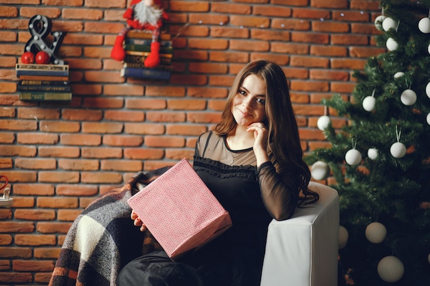 Piękna dziewczyna siedzi w boże narodzenie pokoju