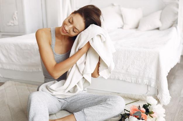 Piękna dziewczyna siedzi w domu blisko łóżka