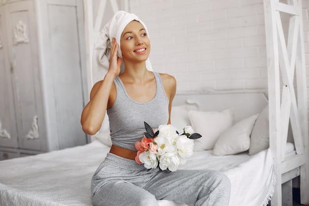 Piękna dziewczyna siedzi w domu na łóżku