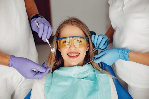 Piękna dziewczyna siedzi w gabinecie dentystycznym