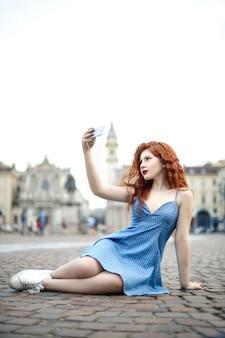 Piękna dziewczyna siedzi w kwadracie, robi selfie z jej smartphone