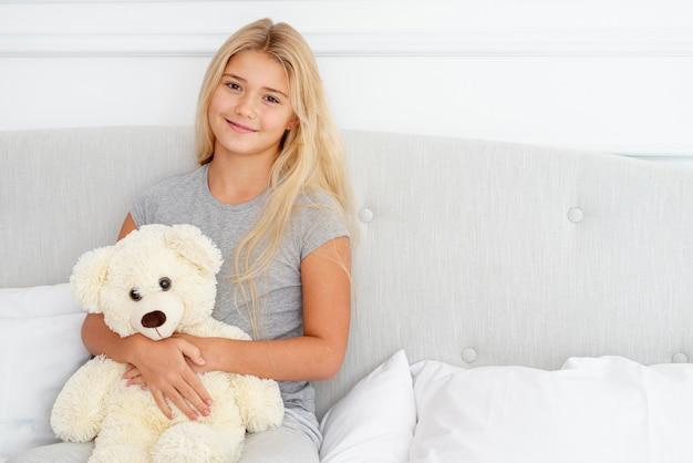 Piękna dziewczyna siedzi w łóżku z jej misiem