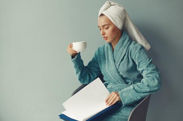 Piękna dziewczyna siedzi w niebieski szlafrok
