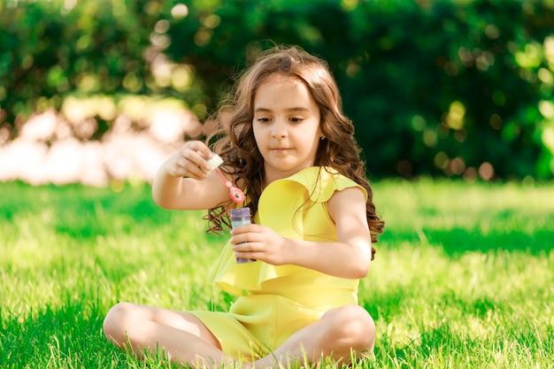 Piękna dziewczyna siedzi w parku na trawie i dmuchanie baniek. zdjęcie wysokiej jakości