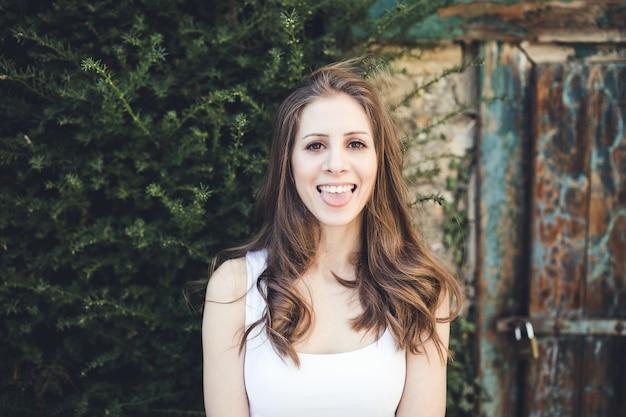 Piękna dziewczyna siedzi w pobliżu domu rolnika, uśmiechając się i wystawiając język