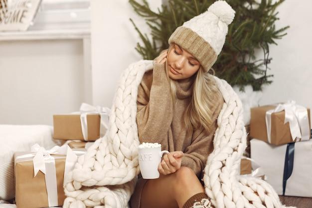 Piękna dziewczyna siedzi w studio z prezentami