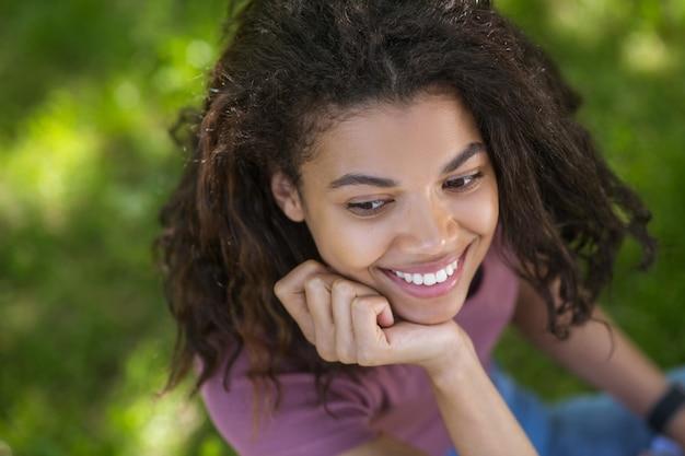 Piękna dziewczyna. śliczna ciemnoskóra młoda dziewczyna ładnie się uśmiecha