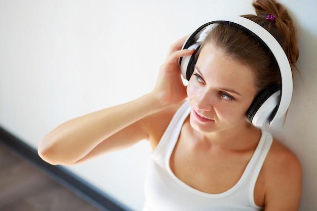 Piękna dziewczyna słucha muzyka z hełmofonami podczas gdy siedzący na podłoga