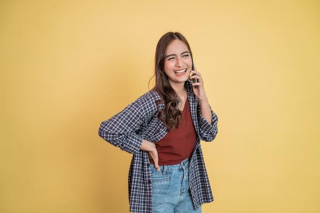 Piękna dziewczyna słucha rozmowy za pomocą telefonu komórkowego śmiejąc się radośnie