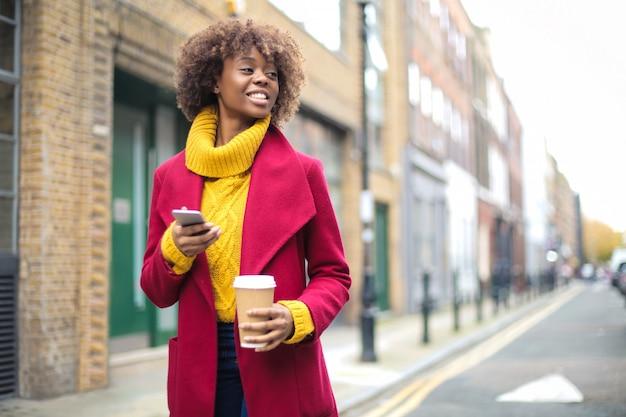 Piękna dziewczyna spaceru na ulicy, picia kawy