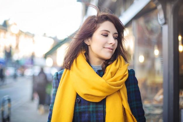 Piękna dziewczyna spaceru na ulicy, ubrany w żółty płaszcz