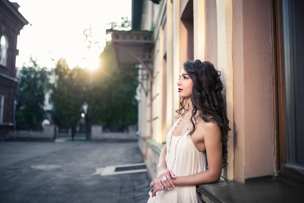 Piękna dziewczyna spaceru w ciepły słoneczny dzień w mieście. młoda brunetka piękna kobieta, koncepcja stylu życia