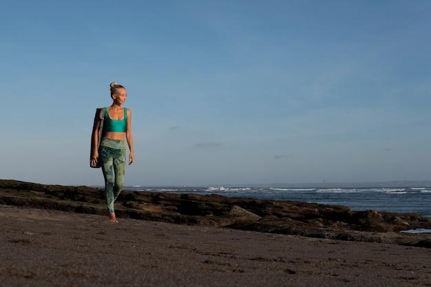 Piękna dziewczyna spacerująca po plaży z matą do jogi