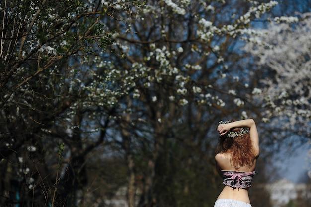 Piękna dziewczyna spaceruje po bujnym ogrodzie ubrana w wieniec