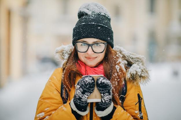Piękna dziewczyna spaceruje po mieście zimą przy filiżance kawy