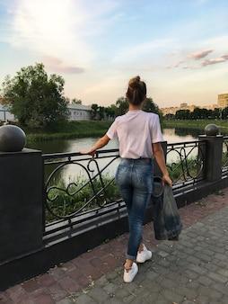 Piękna dziewczyna spaceruje wzdłuż brzegu rzeki
