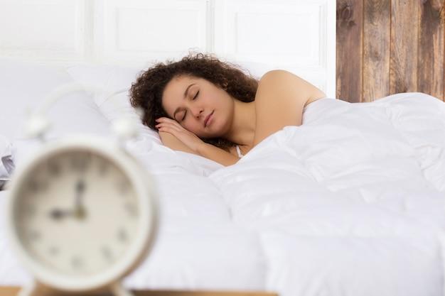 Piękna dziewczyna śpi w łóżku sama. na pierwszym planie biały budzik jest zamazany. godzina 9.