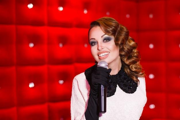 Piękna dziewczyna śpiewa karaoke w klubie nocnym
