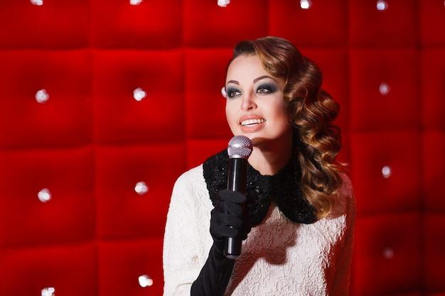 Piękna dziewczyna śpiewa karaoke w nocnym klubie