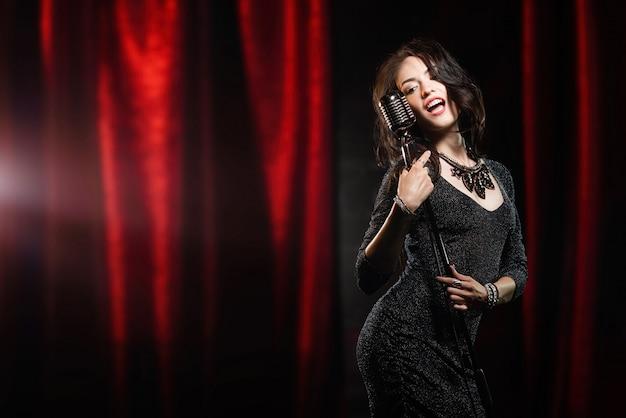 Piękna dziewczyna śpiewa w mikrofonie w sali koncertowej w czarnej sukni