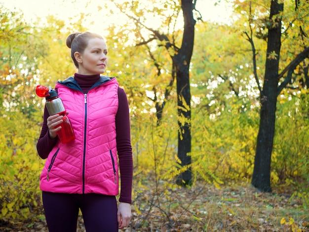 Piękna dziewczyna sport fitness w sportowej z butelką wody lub napoju izotonicznego w dłoni w lesie jesienią.