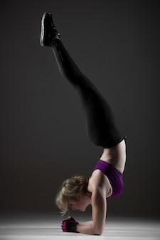 Piękna dziewczyna sportowa robi handstand