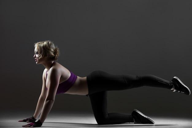 Piękna dziewczyna sportowa robi huśtawki nóg