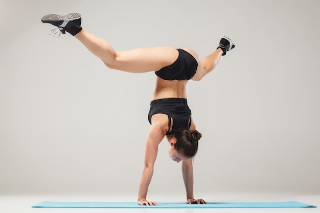 Piękna dziewczyna sportowy stojąc w pozie akrobata lub asana jogi