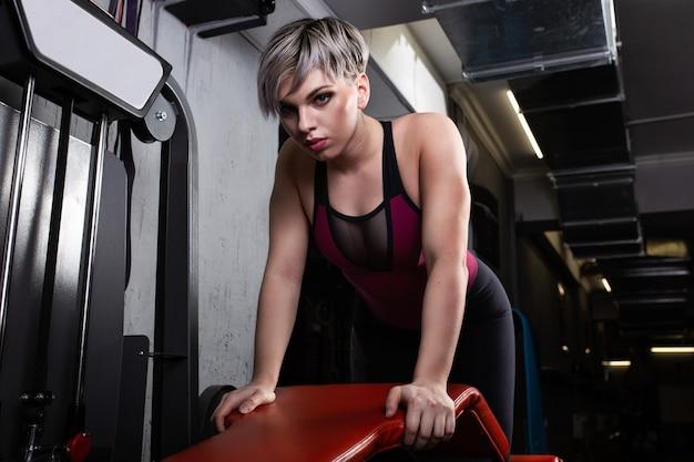 Piękna dziewczyna sportu jest zaangażowana na symulatorze na siłowni