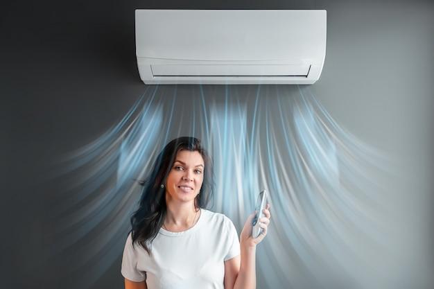 Piękna dziewczyna stoi pod klimatyzacją i strumieniem świeżego zimnego powietrza na szarej ścianie. pojęcie ciepła, chłodnego powietrza, chłodzenia, świeżości.