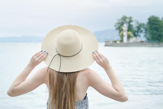 Piękna dziewczyna stoi przy molo. w oddali morze i mała latarnia morska. widok z tyłu