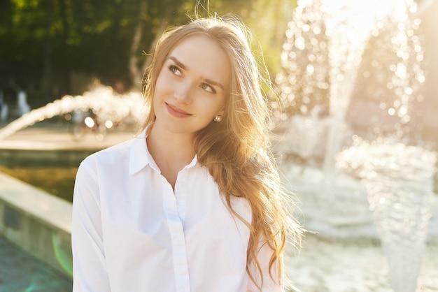 Piękna dziewczyna stoi przy słonecznej fontannie i uśmiecha się.