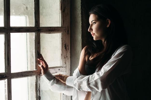 Piękna dziewczyna stoi w pobliżu okna