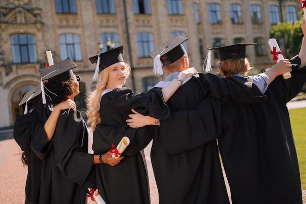 Piękna dziewczyna stoi z przyjaciółmi przed uniwersytetem po ceremonii ukończenia szkoły