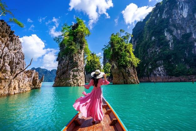 Piękna dziewczyna stojąc na łodzi i patrząc na góry w ratchaprapha dam w parku narodowym khao sok, prowincja surat thani, tajlandia.