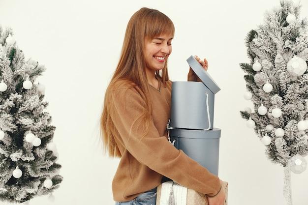 Piękna dziewczyna stojąca w studio z prezentami