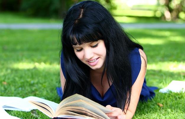 Piękna dziewczyna studiuje w parku