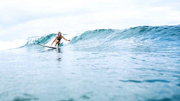 Piękna dziewczyna surfer jazda na desce