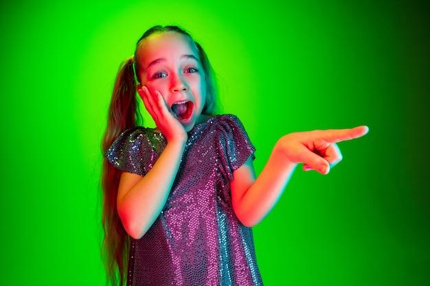 Piękna dziewczyna szuka zaskoczony na białym tle na zielonej ścianie