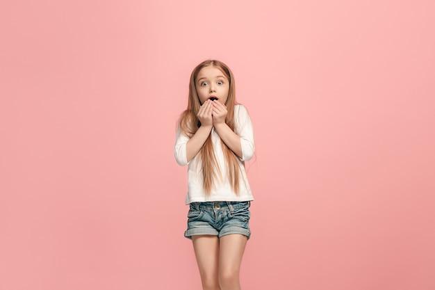 Piękna dziewczyna szuka zaskoczony na różowym tle