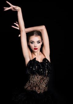 Piękna dziewczyna tancerz towarzyski w eleganckiej pozie czarna sukienka na czarno