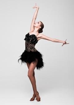 Piękna dziewczyna tancerz towarzyski w eleganckiej pozie czarna sukienka na szaro
