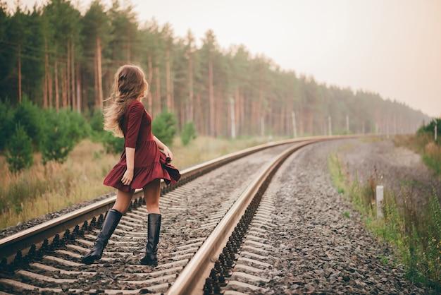 Piękna dziewczyna tańczy z kręconymi naturalnymi włosami cieszyć się przyrodą w lesie na kolei.