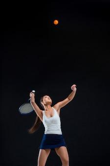 Piękna dziewczyna tenisista z rakietą na ciemnym tle