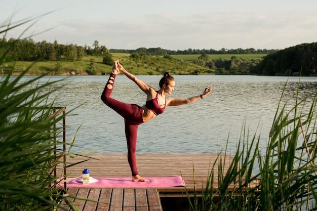 Piękna dziewczyna trenuje na brzegu rzeki. ćwiczy jogę, robi asany.