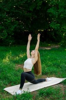 Piękna dziewczyna trenuje na łonie natury i medytuje. rzuca się